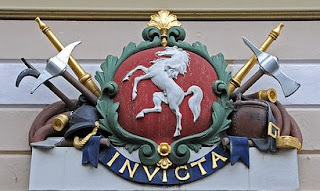 Invicta on the shield above the entrance to the old post office in Canterbury High Street