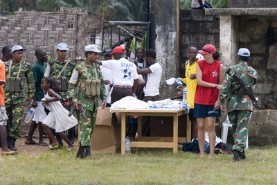 UN Soldiers supervise the distribution of football shirts