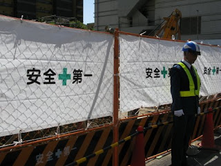 Security guard at accident site with Safety First slogans.