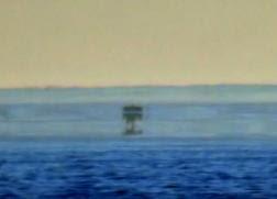 ثلاثة زوارق في الصورة،الحقيقي وصورة وهمية مشوهة عنه في الأسفل وصورة وهمية ثالثة معكوسة عنه في الوسط، وهكذا يبدو كأنه سفينة قديمة من عالم آخر