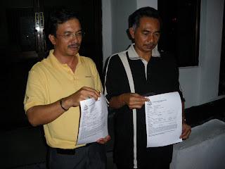 YB Halim (berbaju kuning) dan YB Zakaria menunjukkan repot polis yang telah dibuat mereka di Ibu Pejabat Polis Daerah Kuala Terengganu awal pagi ini