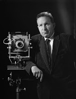 A photograph of Bouchard in a suit, posed next to a camera.