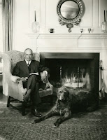 A black and white photograph of man seated with a book in front of a fire. A large dog is on the rug in front of him.