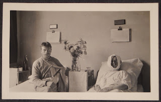 A photograph of two men in side-by-side hospital beds.