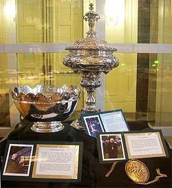 A color photograph of an elaborate silver cup, bowl, and medal, arranged on a black display cloth with plaques.