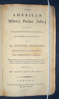 """A photograph of the title page for """"The American Military Pocket Atlas,"""" dated 1776 in pencil."""
