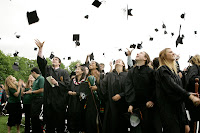 A color photograph showing a crowd of people outside in black gowns, throwing graduation caps in the air.