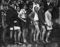 A black and white photograph of a group of men in shorts crowded together.