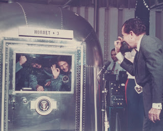 "A photograph of Nixon exchanging ""OK"" gestures with crew members behind glass."