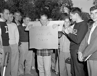 "A photograph of a crowd of men. In the middle, a young man is stuck in a stock and holding a sign reading ""I wouldn't wear my beanie."""