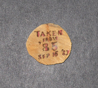 "A circular piece of can. The words ""Taken from '85 Sep 16 '81"" are written on it."