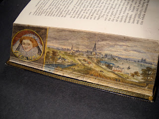 The bent fore edge of a book, which reveals a landscape and portrait of Queen Elizabeth.