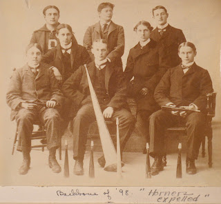 A photograph of eight seated men. Some are visibly holding small horns. One seated centrally has a horn a few feet long resting against his leg.