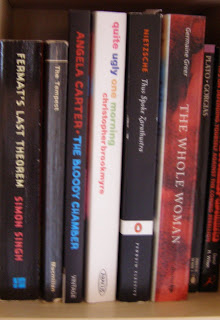 Some red and black books with a colourful one in the middle