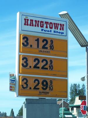 sign at gas station displaying prices