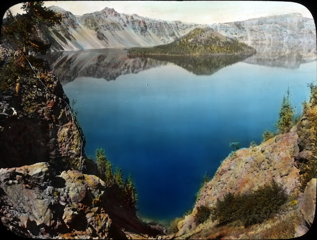 "Image Title: Crater Lake, view from north Image Description: ""Here is an inspiring view of Crater Lake – that which is left of grim old Mt. Mazama – the deepest and bluest lake in the world. It measures two thousand feet in depth and the intensity of its color is almost unbelievable even while you look at it. Many Alpine lakes are blue under some lights. The deep blueness of Crater Lake may possibly be due to mineral which the water holds in solution; yet a glassful of the water is as clear as the clearest. Its cliffs from skyline to surface are a thousand feet high, and its color may be due in part to these surrounding walls and to its enormous depth. From the rim, a narrow margin of the water along the walls appears to be sea-green. The lake has no visible inlet or outlet as it occupies the great cavity left by Mt. Mazama when it disappeared into its own depths. It is a gem of wonderful color in a setting of pearly lavas relieved by patches of pine-green and snow-white—a gem which varies in hue with every atmospheric change and every shift of light. Because of the unique character and extraordinary beauty of this lake called by Joaquin Miller, 'The Sea of Silence,' Crater Lake National Park was established in 1902."" Creator: Fred H. Kiser Date.Original: Circa 1915-1920 Original Format: Lantern slides Original Collection: Visual Instruction Department Lantern Slides. photography-news.com, Photography News, Diana Topan, Crater Lake, Oregon photos, landscape photography"