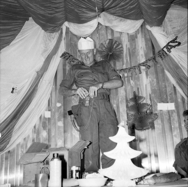 Vietnam. 1965-12-25. Despite Christmas festivities the war is never far away as indicated by the pistol worn by Warrant Officer Harold Smith, Company Sergeant Major, B Company, 1st Battalion, Royal Australian Regiment (1RAR), of Macquarie Fields, NSW. Warrant Officer Smith was just presented with a medal for endurance above and beyond the call of duty during the hectic Christmas Day celebrations.