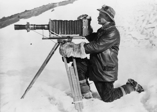 "Herbert George Ponting taking a photo with large camera on tripod during the British Antarctic (""Terra Nova"") Expedition, January 1912. Taken by unidentified photographer. Silver gelatin print. Photographic Archive, Alexander Turnbull Library."