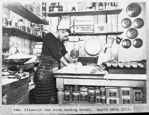 Thomas Clissold the cook making bread during the British Antarctic Expedition of 1911-1913. Shows him in a kitchen surrounded by equipment and supplies. He wears hat and apron and is kneading dough on a table. Griffiths McAllister & Co containers of bacon rations, beed marrowfat, cod roes, ground cinnamon, celery seed, sago, and washing soda, are visible in the foreground. Photograph taken on the 26th of March 1911 by Herbert George Ponting.