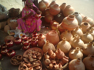 A Woman gives finishing touches to the pots in Jaipur
