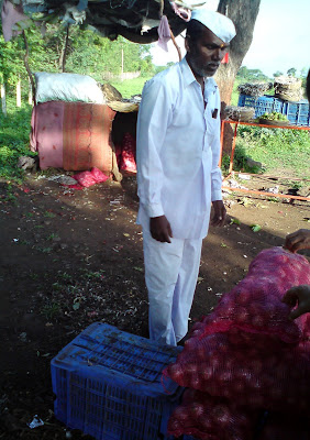 A farmer sells Onions on the Mumbai-Nashik highway