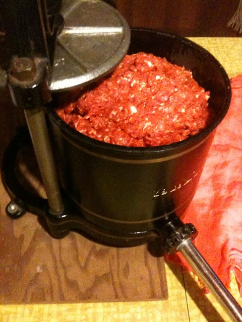 An old sausage press full of ground pork