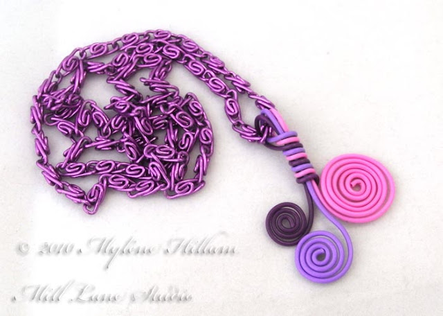Pink and purple spiral wire pendant on a purple aluminium chain.