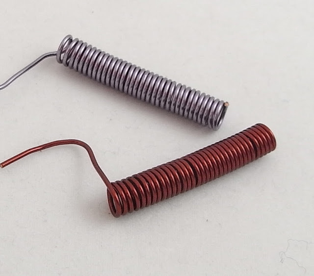 Mauve coil and rust coil of waiting to be cut into jump rings.