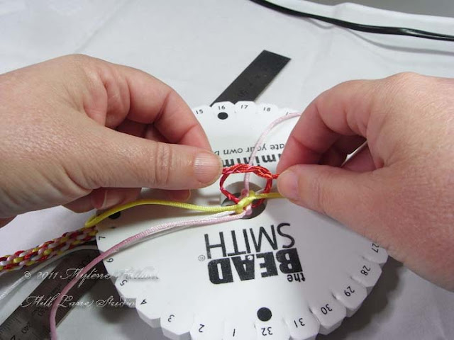 Kumihimo basics: tie off the threads on the disk before removing the cords from the slots so that it doesn't unravel.