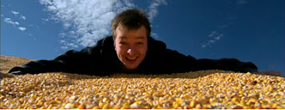 Photo of Curt Ellis atop a huge pile of corn, courtesy of King Corn