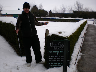 Minigolfer Richard Gottfried attempting to play on the snowed under Crazy Golf course at Tea Green Golf, Wandon End, Luton