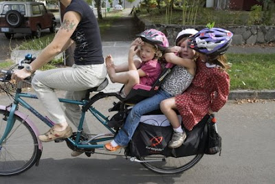 Image of three kids on a bicycle rack