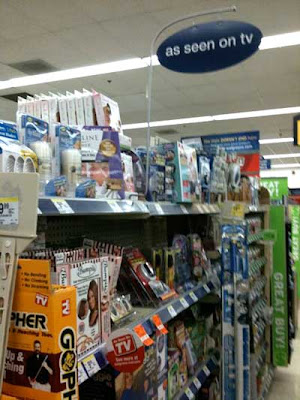 Store shelves crammed with products, sign above says As Seen on TV