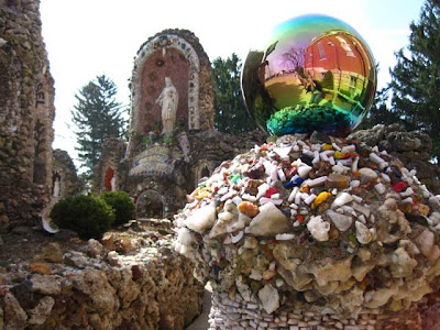 Irridescent gazing ball amid rock-covered structures with a statue of Jesus in the background
