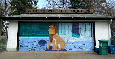 Surburban garage door painted with a mural of an adult Simba with Nala. On the roof of the garage is a wooden sign that says Joy to the World the Lord Is Come