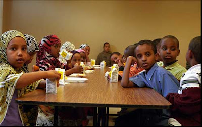 Somali elementary students at lunch, girls in headscarves, color photo