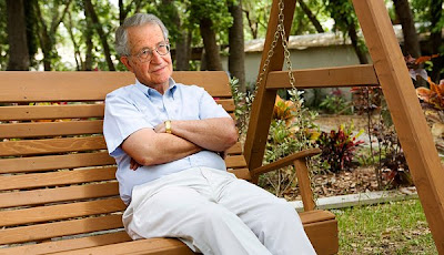 Noam Chomsky sitting on a wooden swing bench