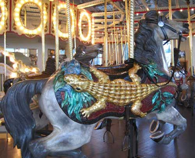 Carousel horse with a gold leaf alligator on its side