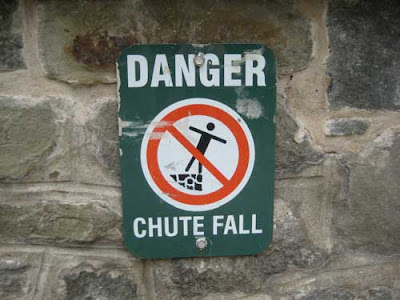 Sign that says DANGER chute fall with figure falling off a stone wall