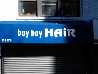 Blue awning with white letters reading Buy Buy Hair