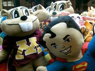 Square-featured Superman doll face pressed up against the glaass, surrounded by other dolls