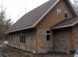 Exterior shot of a cord wood house -- looks very cozy!