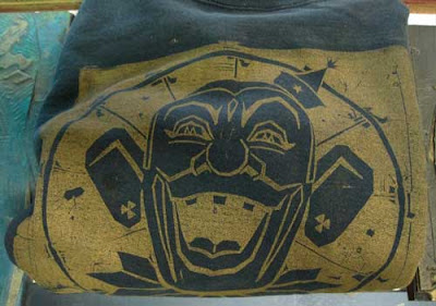The clown printed in gold ink on a dark sweatshirt