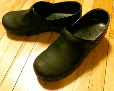 A pair of black Dansko clogs on a maple wood floor