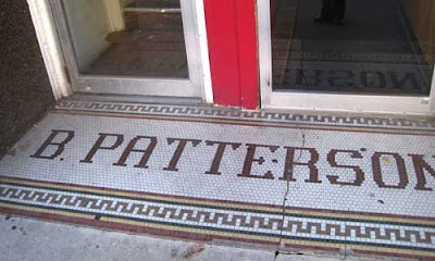 B. Patterson in dime tile outside a business door