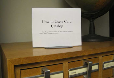 Small sign atop a wooden card catalog, reading How to use a card catalog
