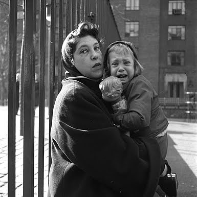 1950s photo of woman in scarf holding a crying preschooler