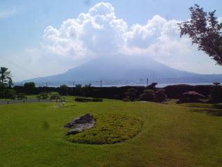 手前は仙巌園の庭園。バックには青い空と雲が少しある桜島