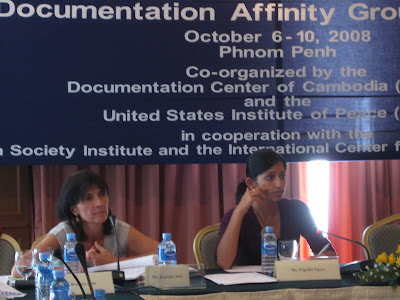 Woman plus Vijaya seated under a banner about the documentation affinity group at a table for speaking