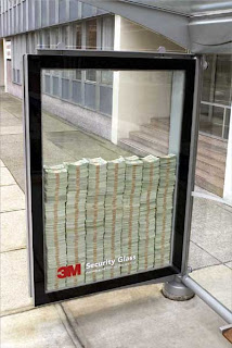 picture of a lot of money behind a security glass in front of a building